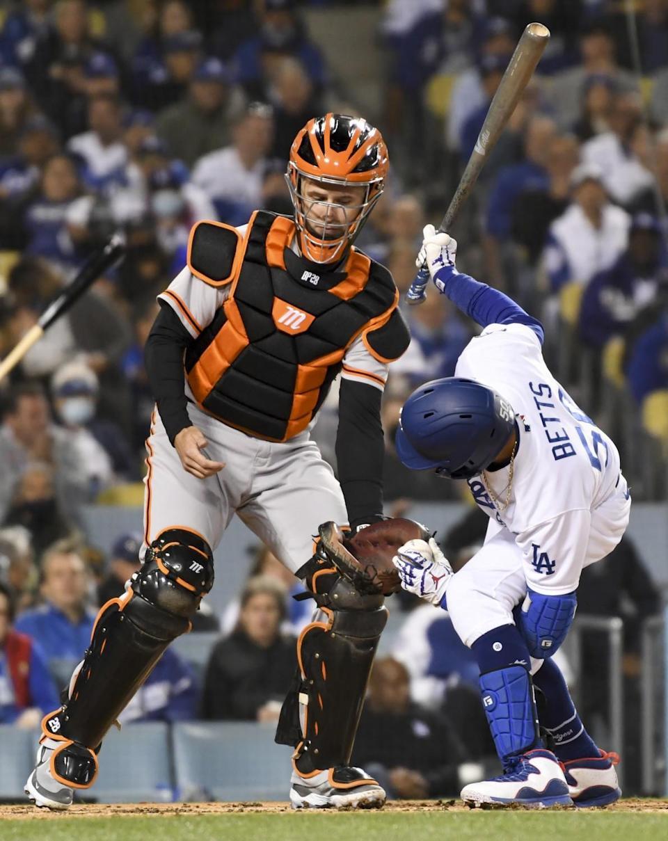 Dodgers' Mookie Betts hands the baseball between his legs to Giants catcher.