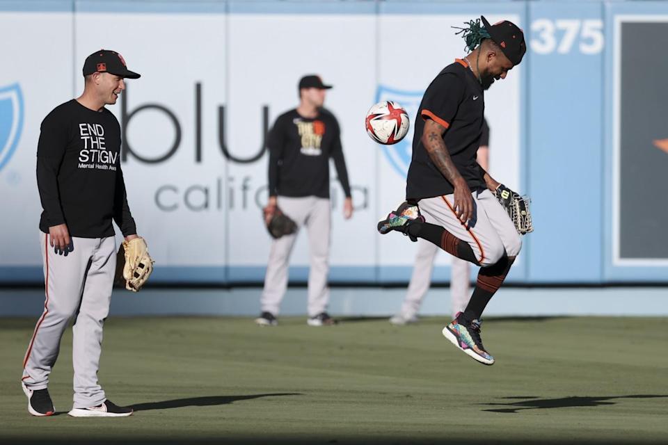 Giants' Camilo Doval kicks around a soccer ball.